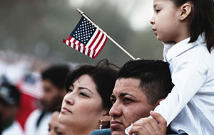 woman and man with a young girl sitting on his shoulder waving an American flag