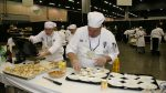 Volunteers backstage plating samples for audience members