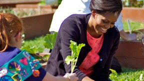 Michelle Obama helps plant herbs with a team of Girl Scouts.