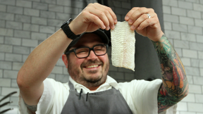 Chef Sean Brock in the kitchen, holding up a fillet of fish