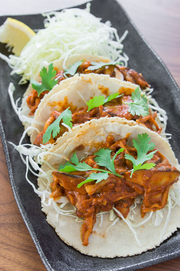 These Braised Mushroom Tacos are quick and easy. The mole is not overly complex, and the mushrooms look almost like shredded chicken.