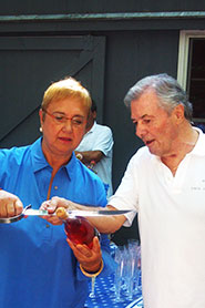Lidia Bastianich and Jacques Pepin cutting the top off a bottle of champagne