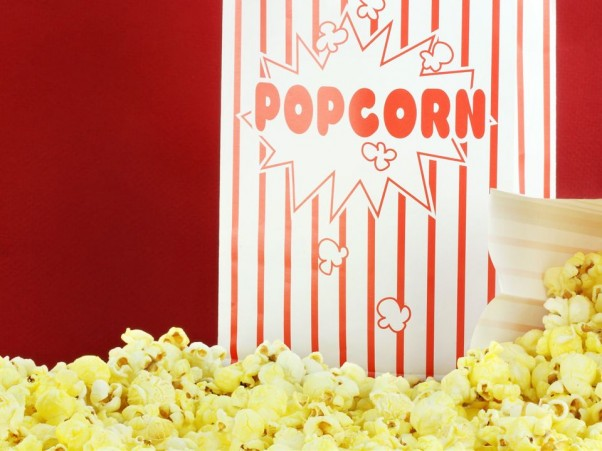 Bags of buttery popcorn against a red background. Room for text.