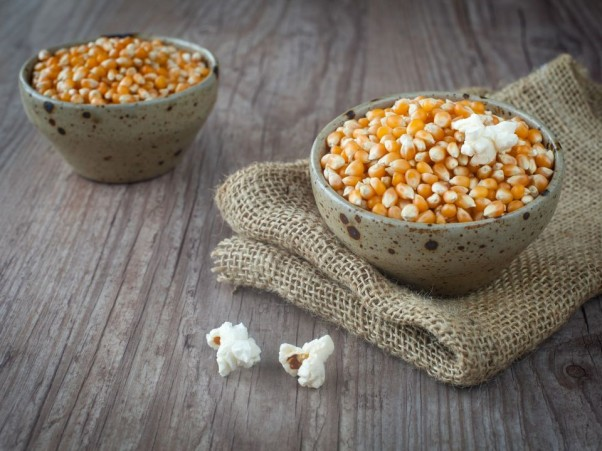 Corn seeds in a bowl on a wooden background