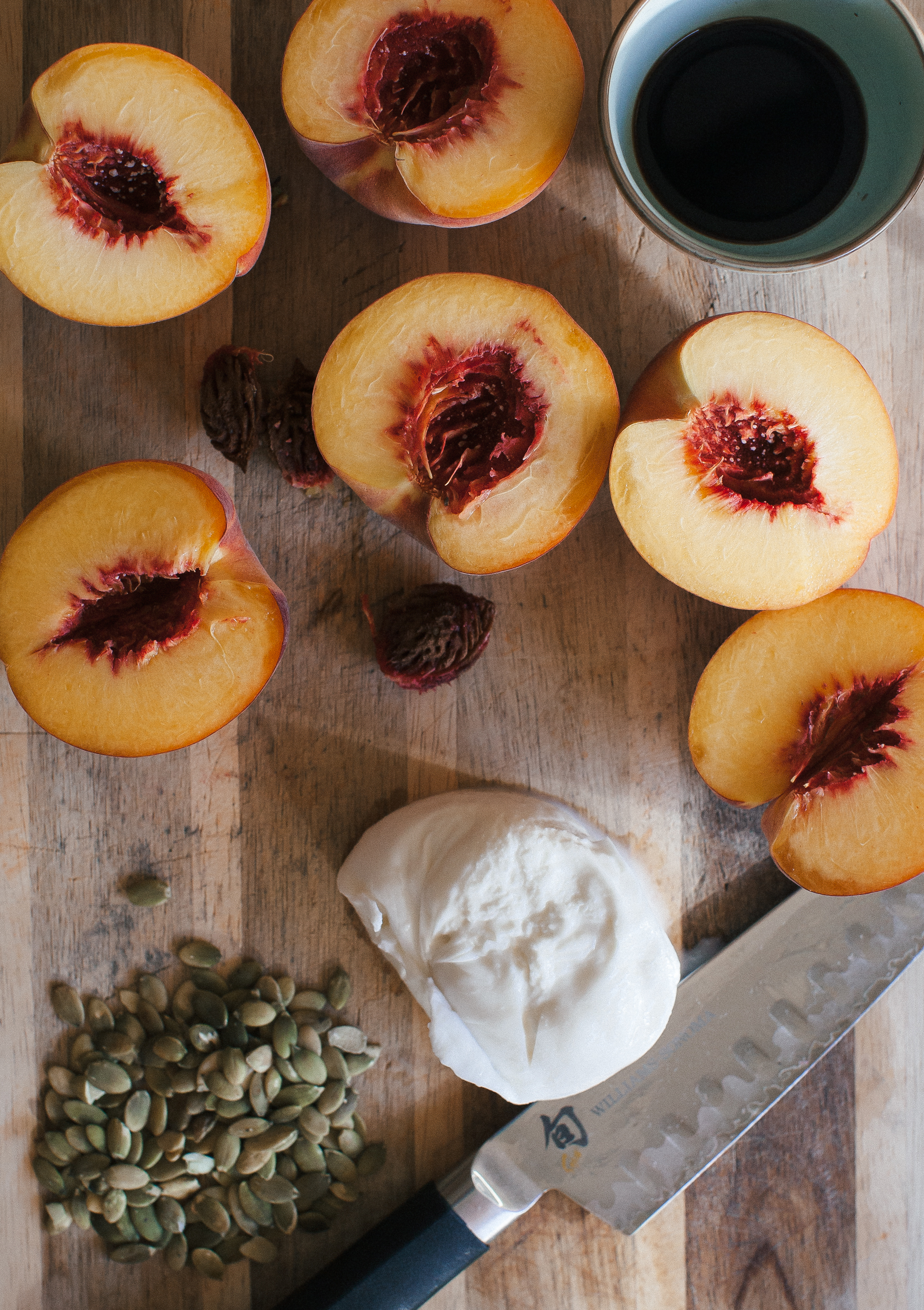 Topped with a balsamic reduction, these Grilled Peaches feature a spoonful of burrata and crushed pumpkin seeds.
