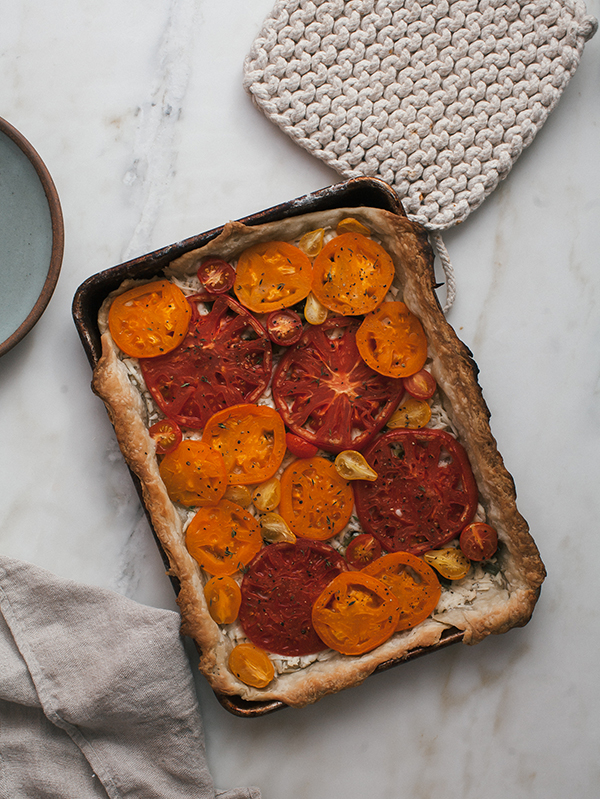 This Cheesy Heirloom Tomato Tart is a simple dish with cheese and onions.
