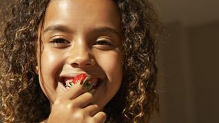 Corbis - Girl Eating Strawberry
