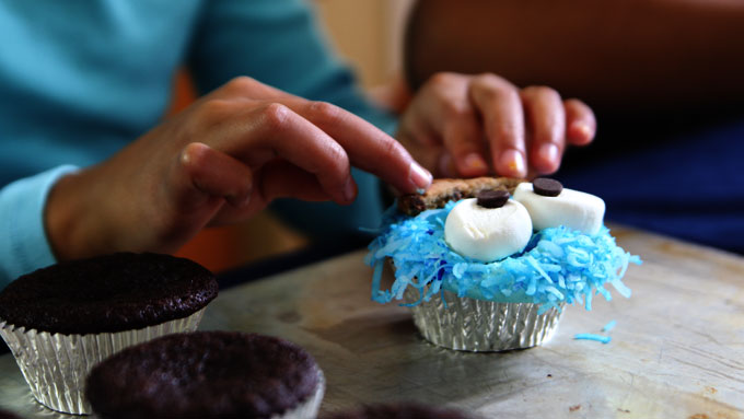 placing-cookie-mouth-on-cupcakes