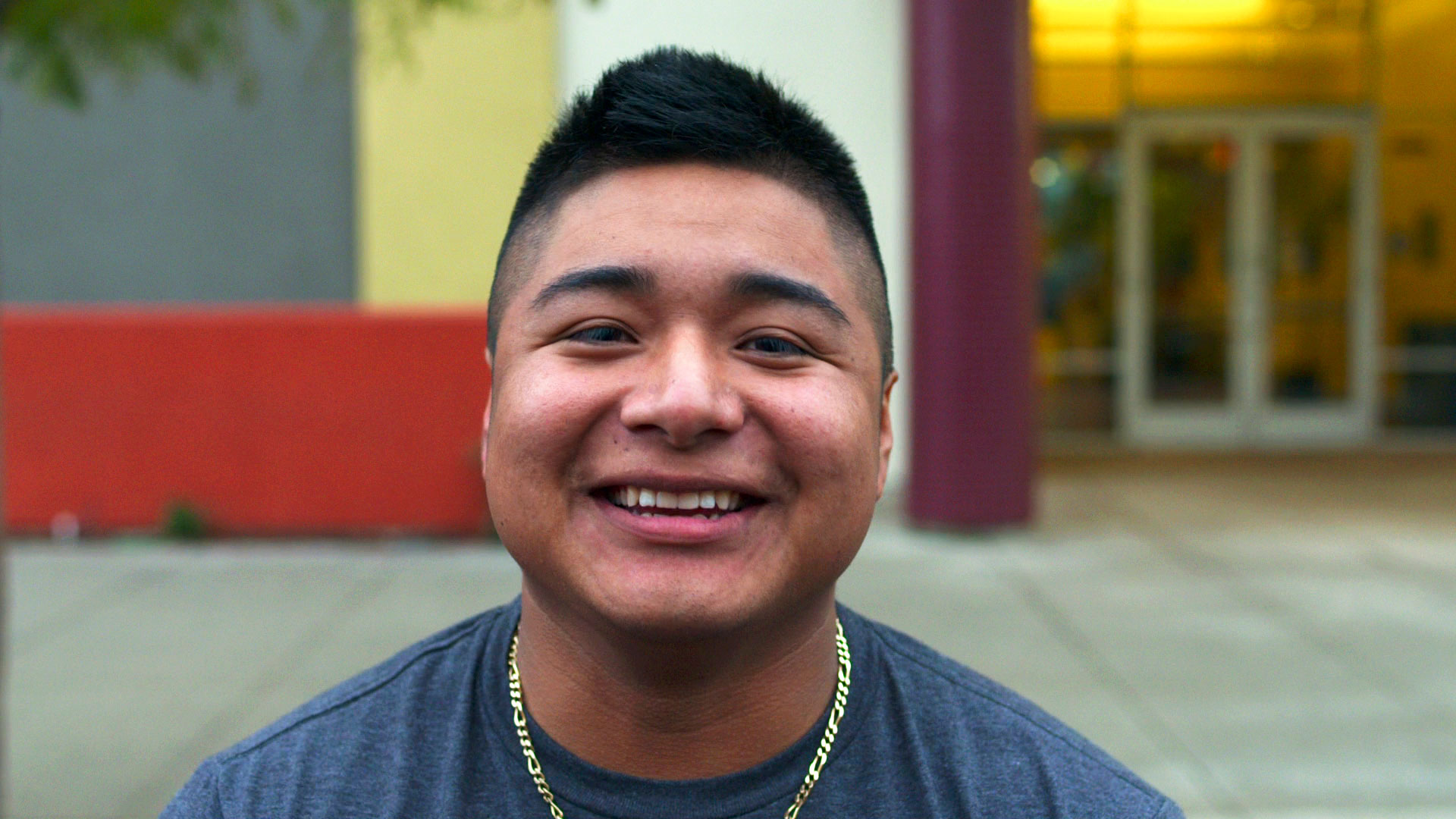 Young Latino man smiles for the camera.
