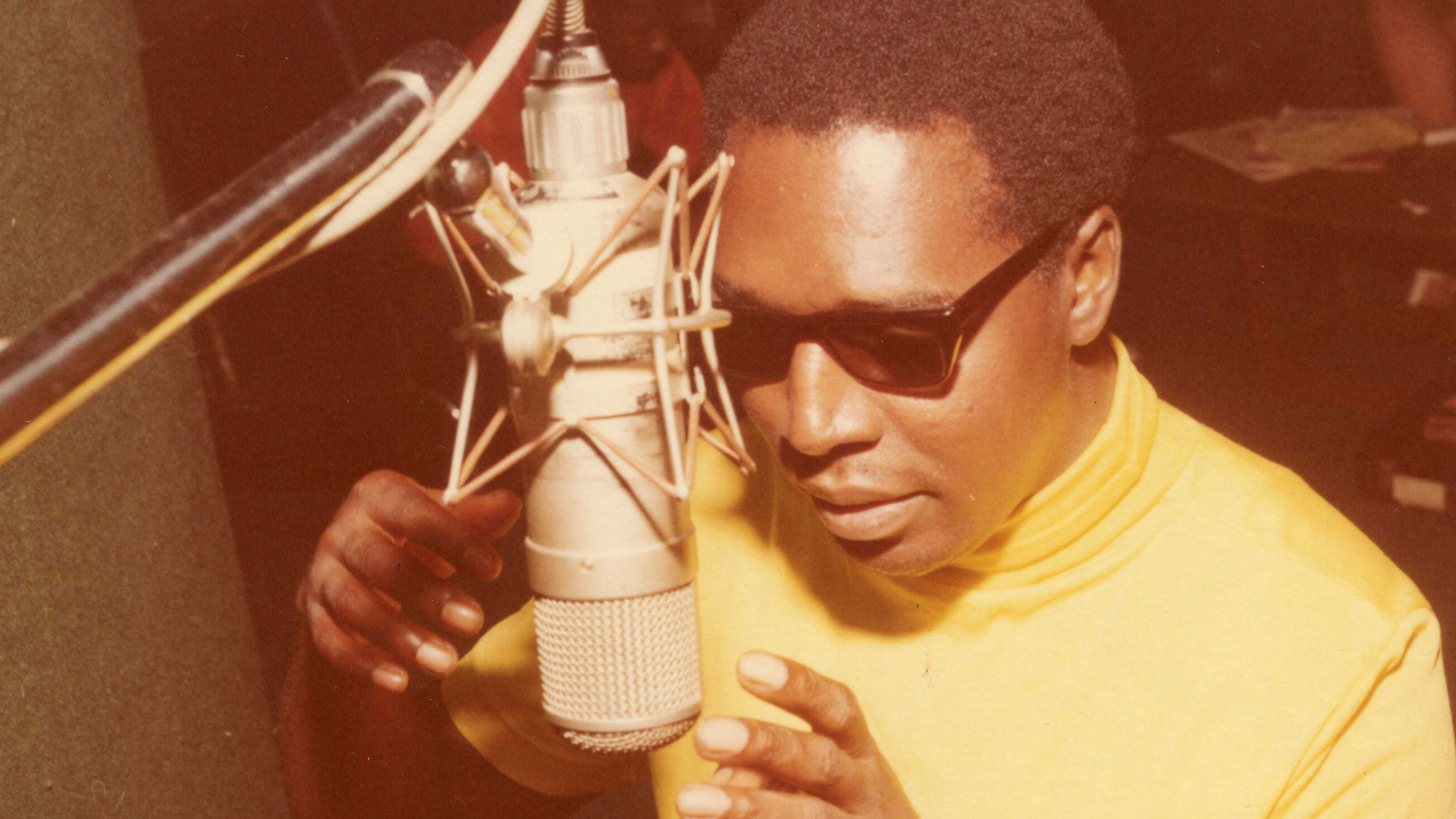 Clarence Carter sings into mic at Muscle Shoals studios.