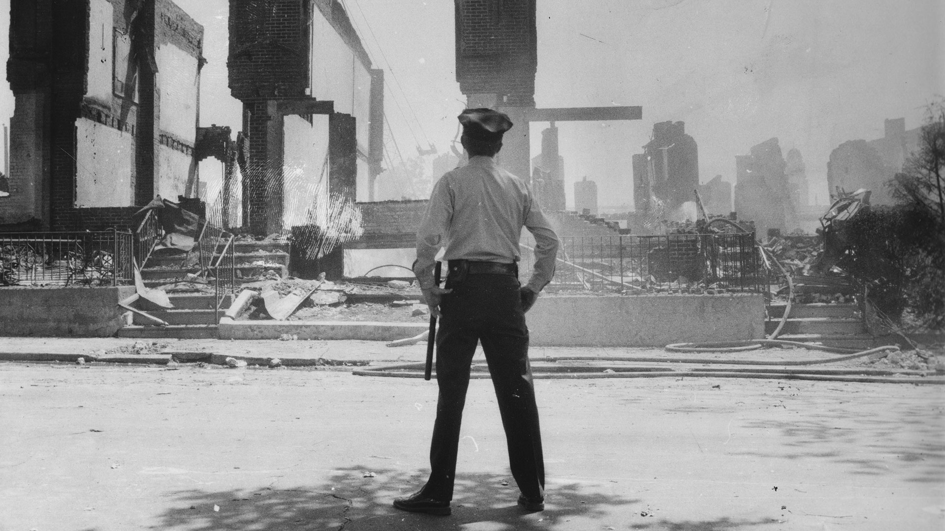 A Philadelphia police officer observes the rubble after the MOVE bombings