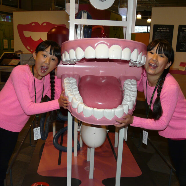 Twin Sisters Mia and Alexandra in a museum with giant wind-up teeth.