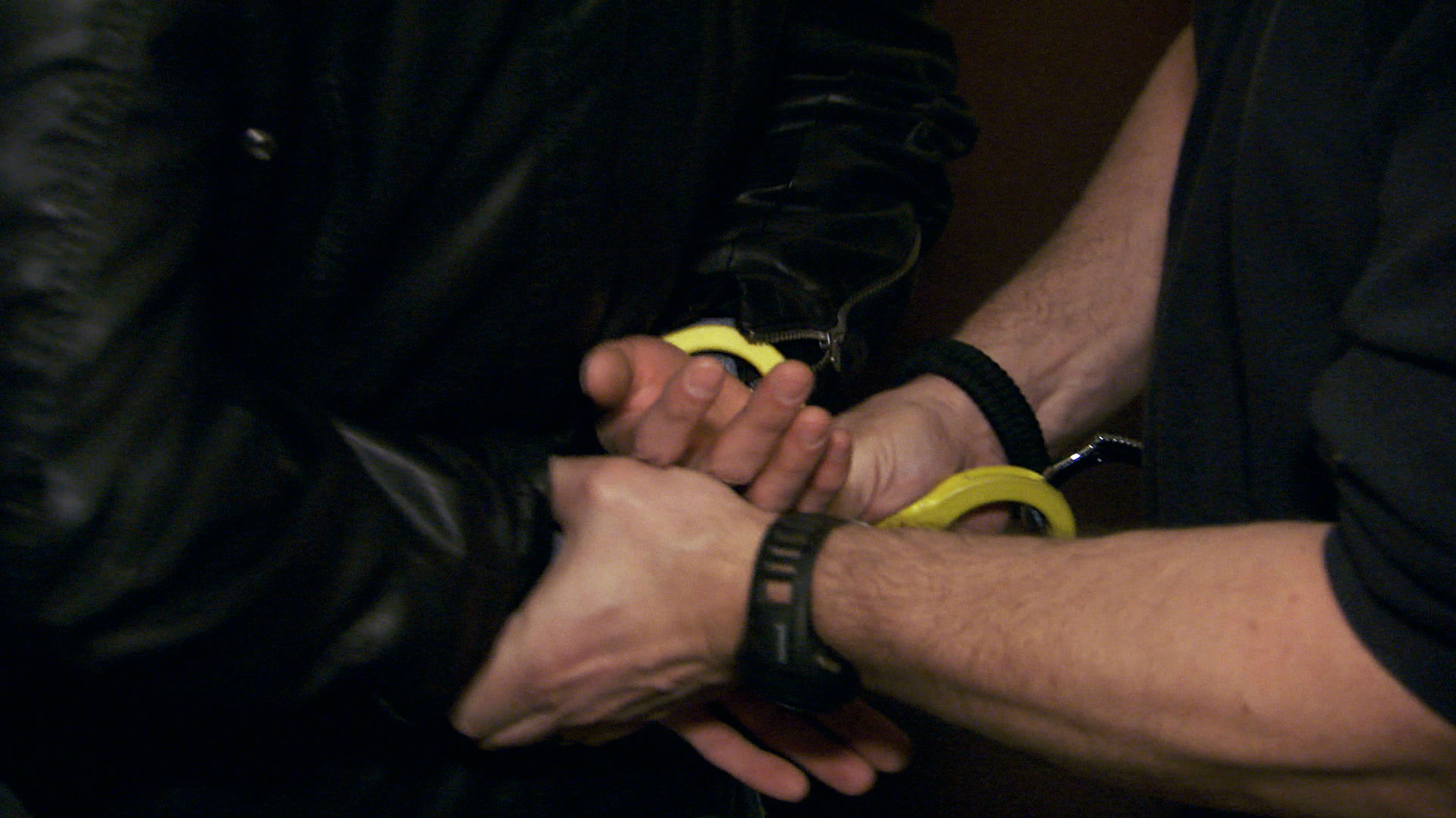 Wrists restrained by yellow handcuffs.