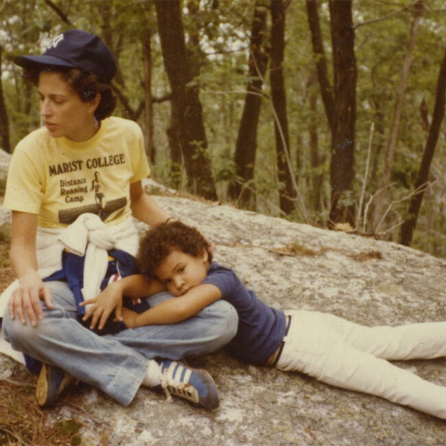 Young Lacey Schwartz lies on her mother's lap in the woods.