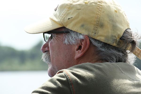 Filmmaker Gregg Mitman, wearing yellow baseball cap looking off