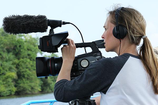 Filmmaker Sarita Siegel looking behind the display screen of a digital video camera