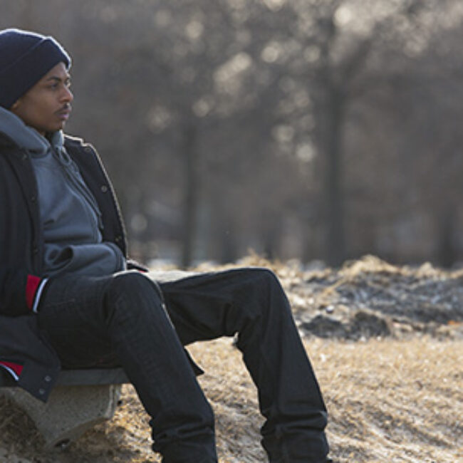 Young African American man sits on a park bench in winter clothing.