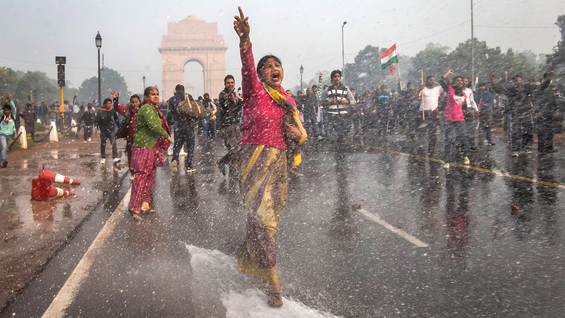 A woman marches down a Delhi street shouting in protest as water cannons shower the scene.