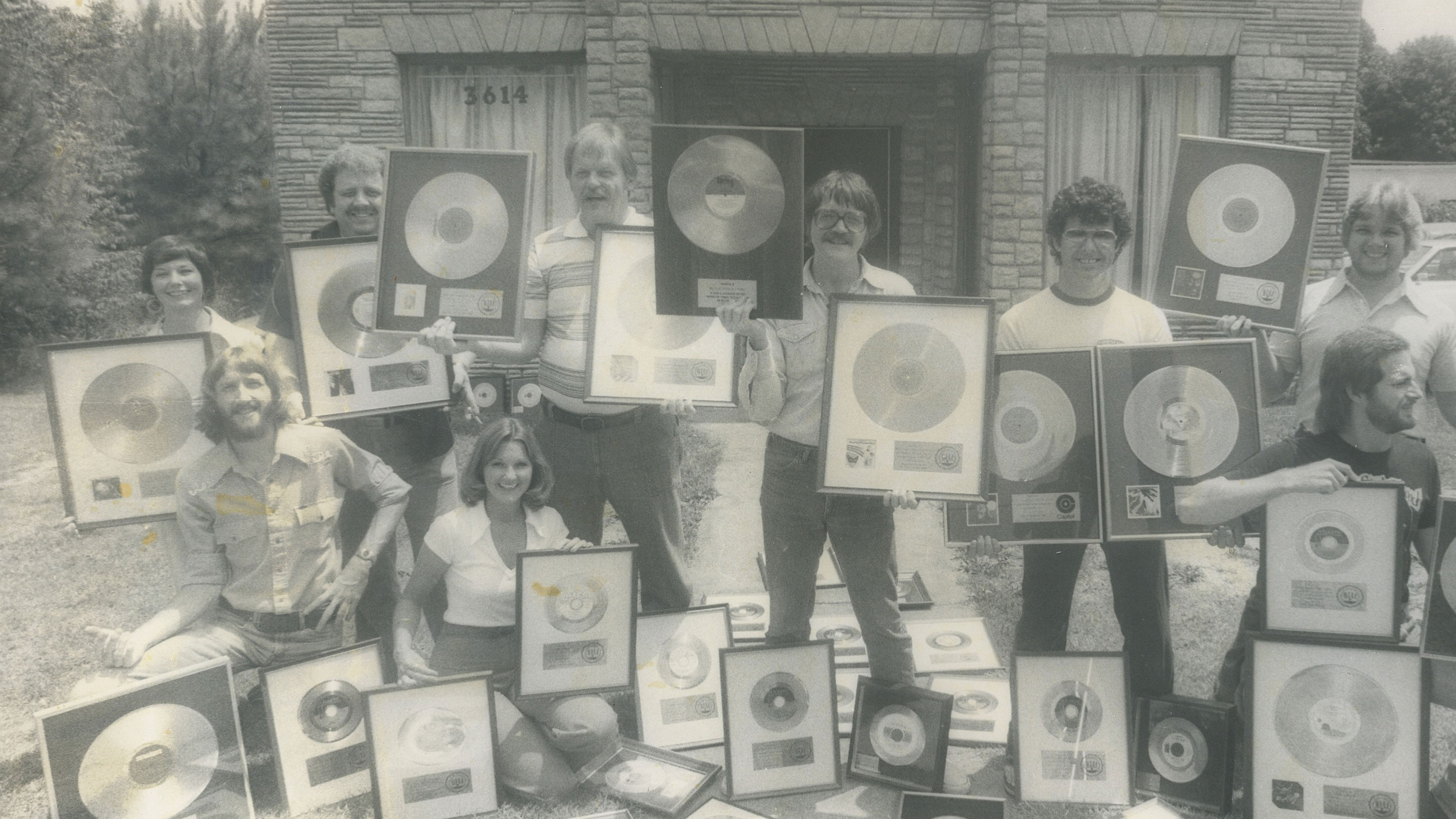 Muscle Shoals staff displaying their gold records.