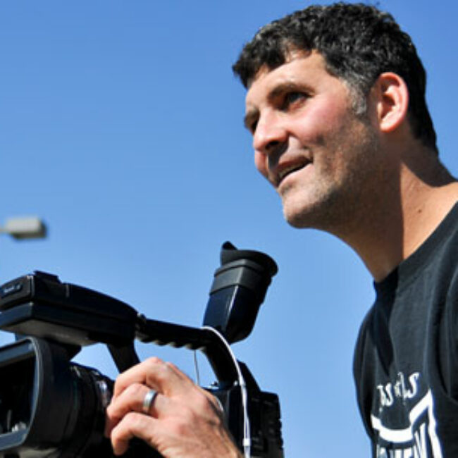 Filmmaker Brad Lichtenstein smiles while framing a shot with a video camera.