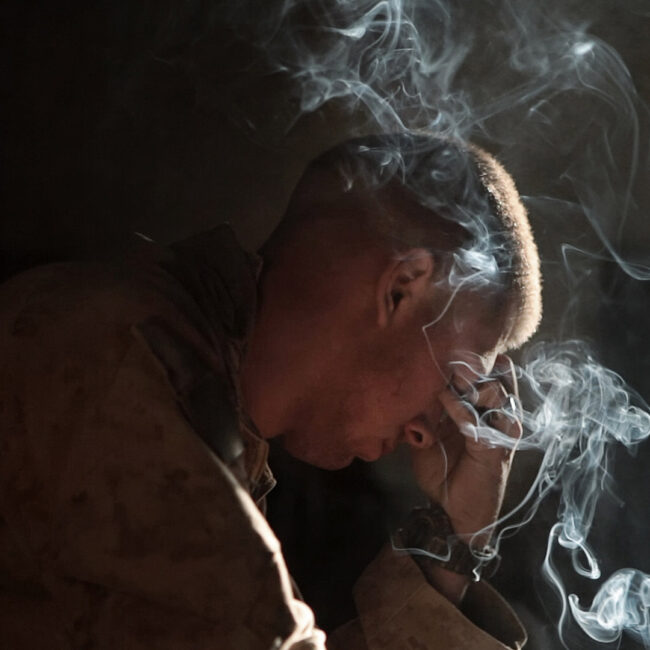 A solider holds his head in his hand with cigarette smoke curling in the air.