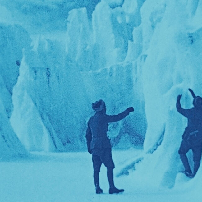 Still frame from The Epic of Everest (1924), men exploring an ice cave on the mountain.