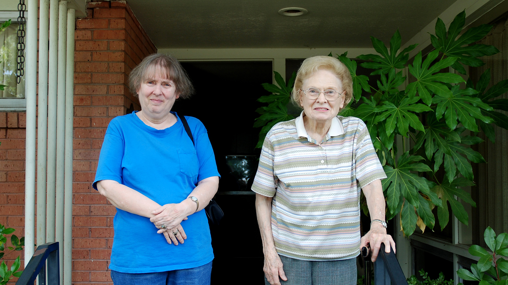Dona and her mother Mimi stand on their suburban Dallas porch