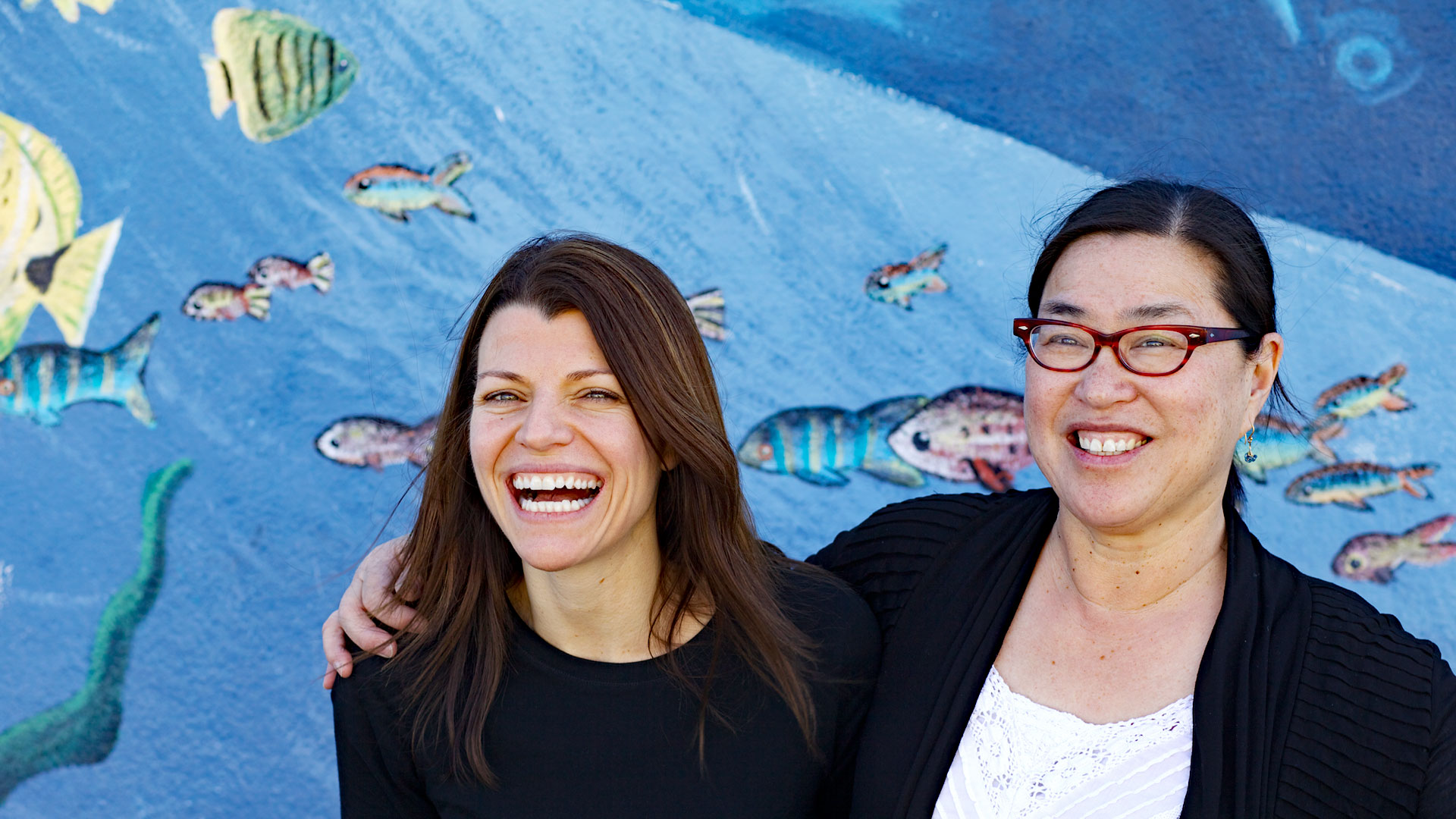 East of Salinas filmmakers Laura Pacheco and Jackie Mow (l-r), in front of a sea-themed mural.