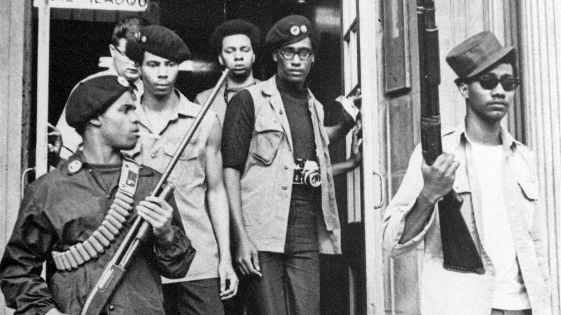 Black Panthers exiting building armed with rifles.