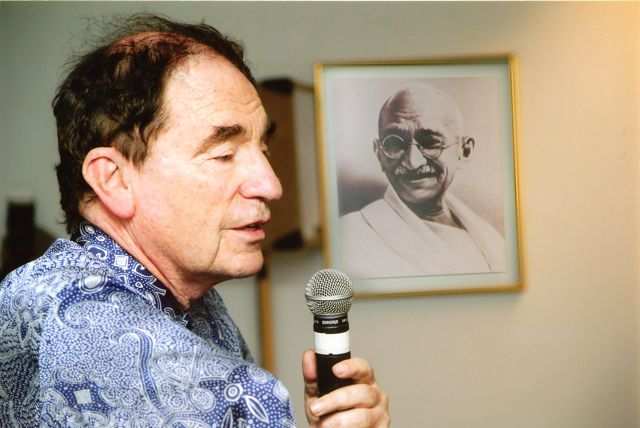 Albie Sachs speaks into a microphone with a portrait of Gandhi behind him