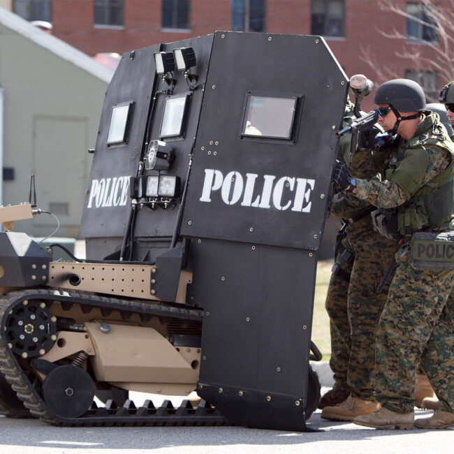 Police in military fatigues huddle behind a SWAT robot