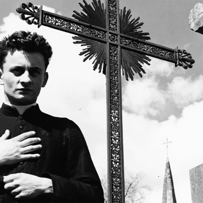Still of priest standing in front of outdoor cross in Robert Bresson's 1951 film Diary of a Country Priest