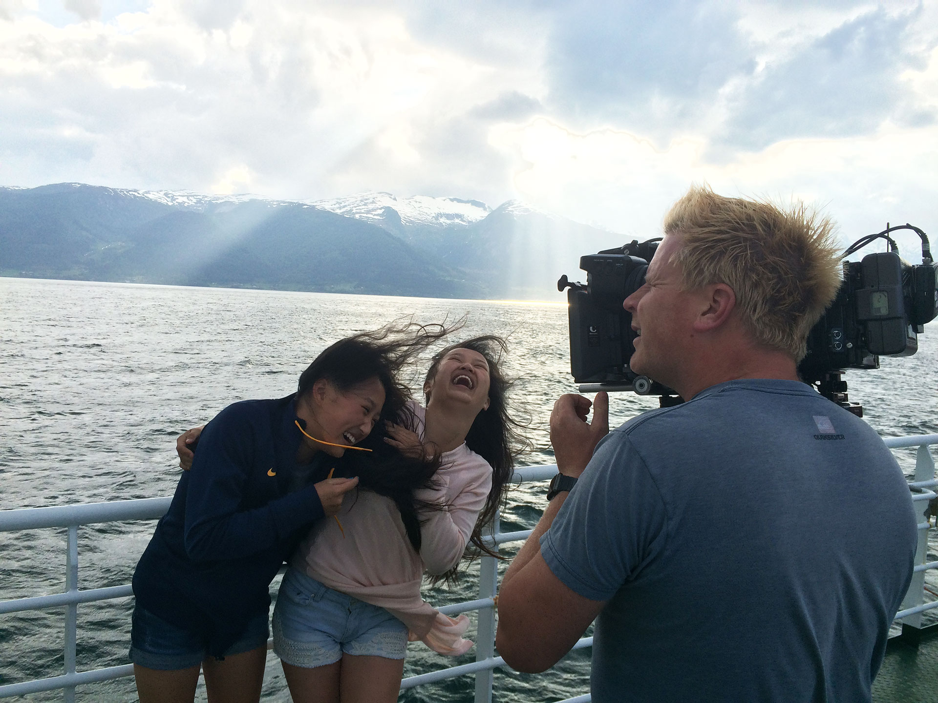 Alex and Mia laugh while a film cameraman shoots them on a boat in Norway