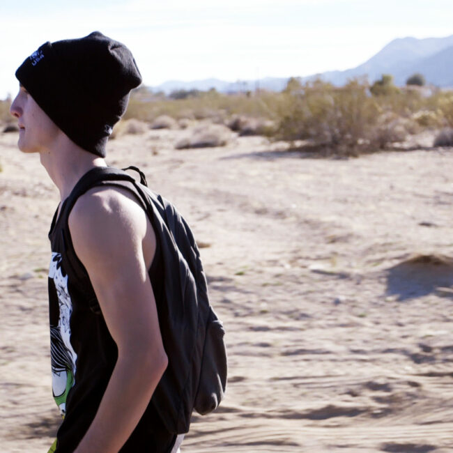 Joey McGee walks down a road in the Mojave Desert.