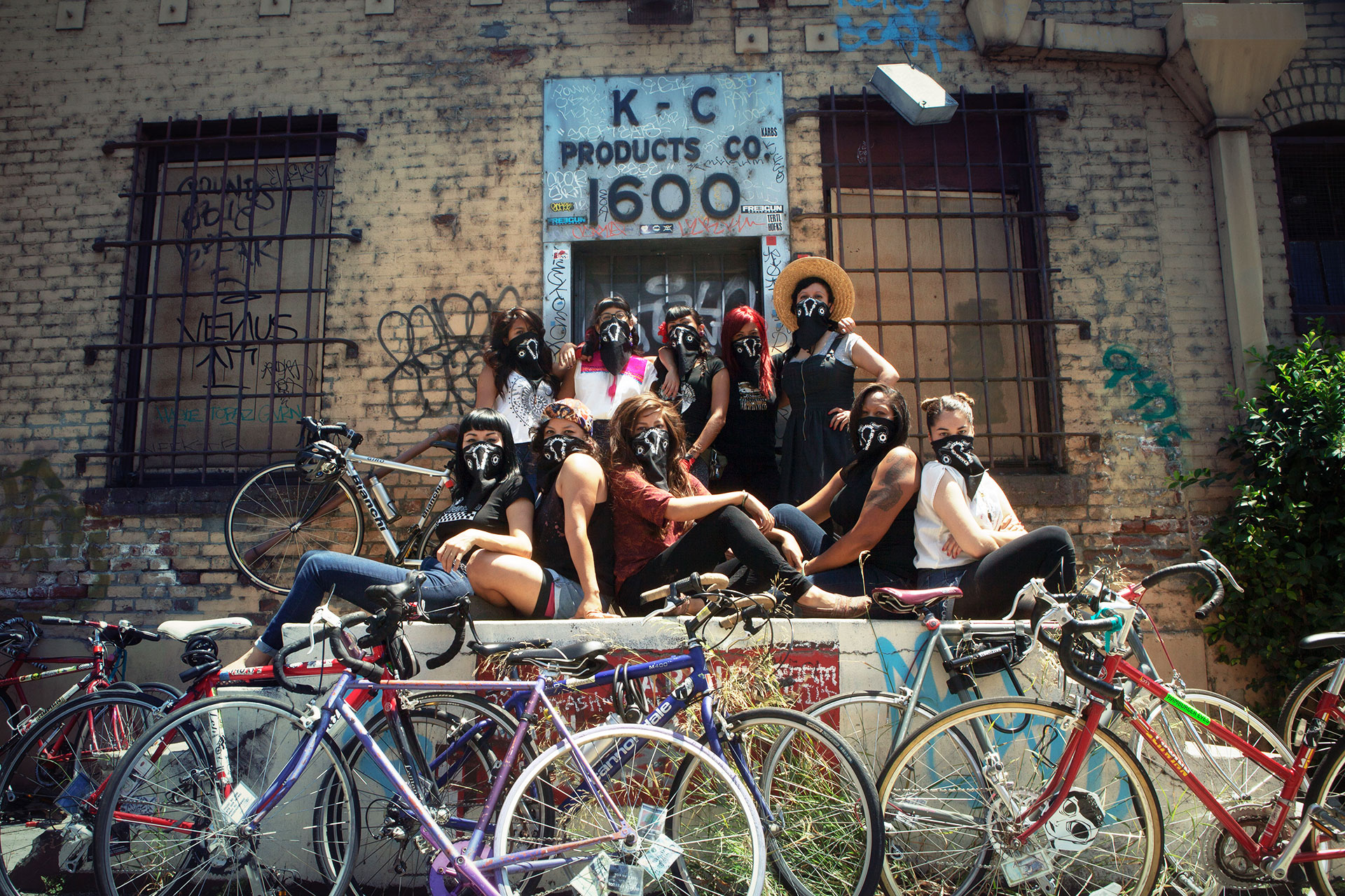 The Ovas bike brigade pose with bikes in front of a warehouse in East Los Angeles