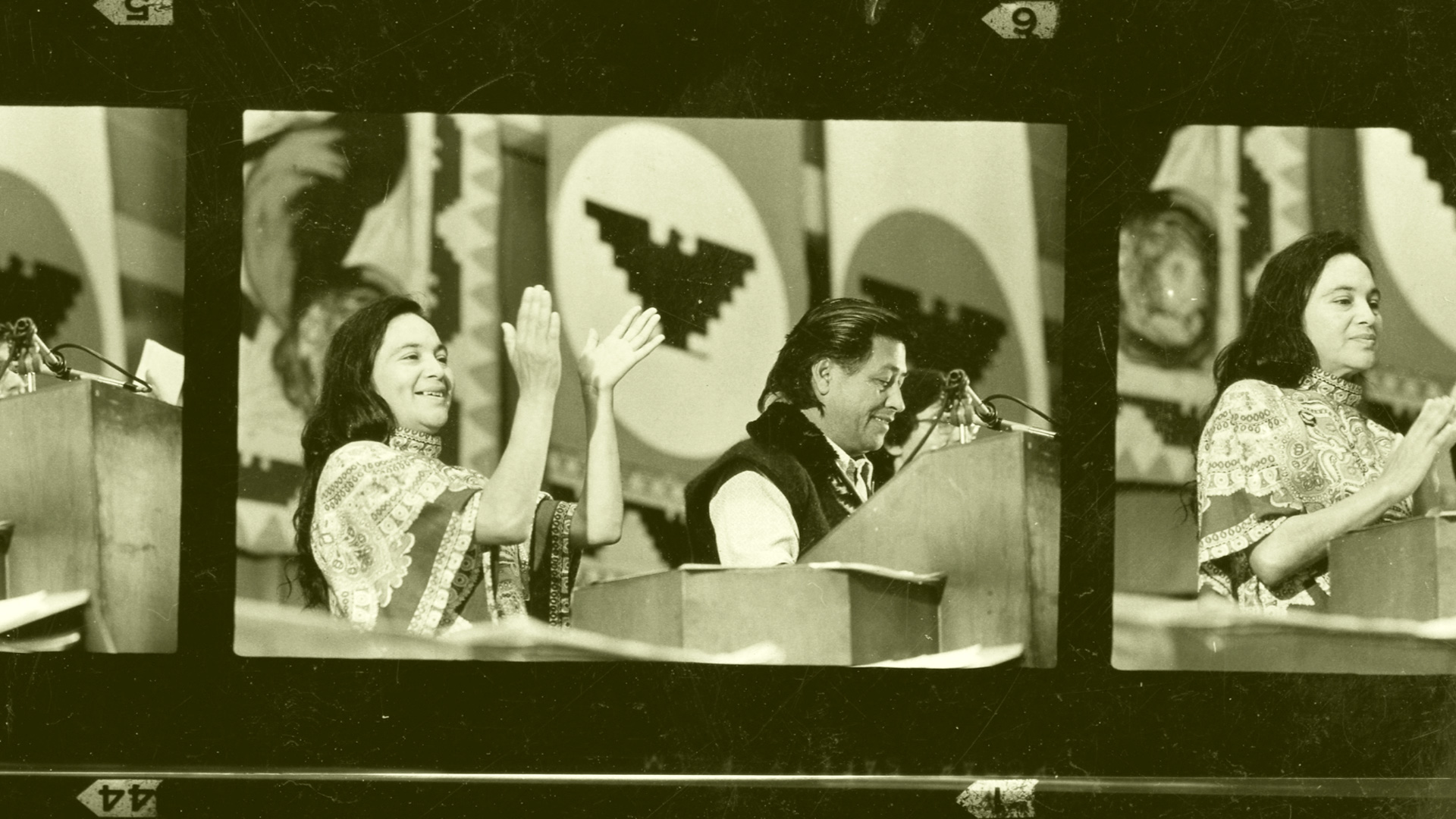 Dolores Huerta, with Cesar Chavez, in public speech from the 60s, in a film strip image