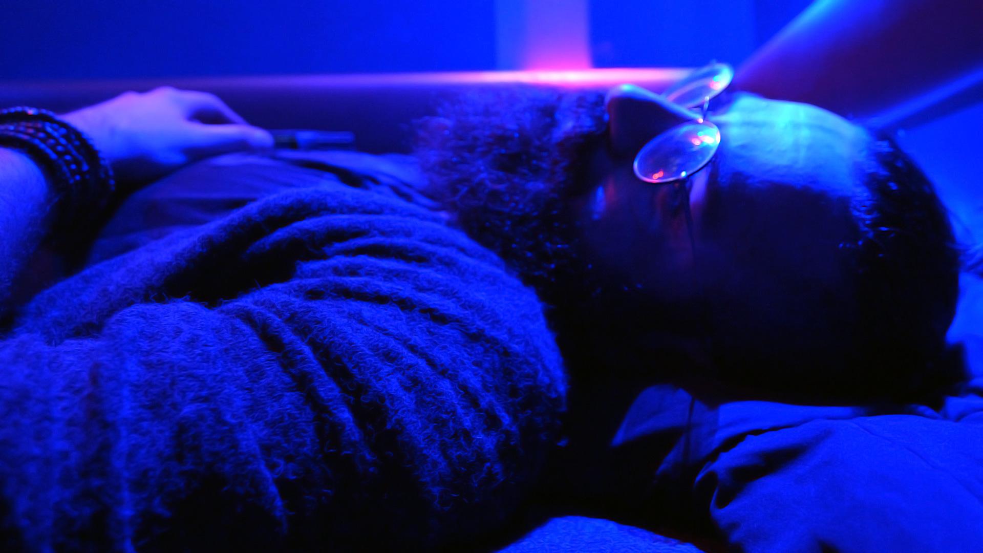 Shahin Najafi resting before concert, in ultraviolet light