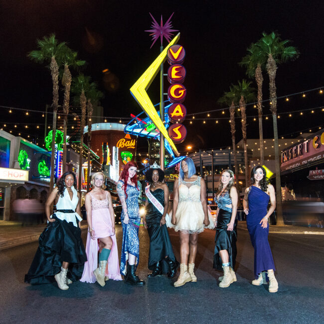 The women of Served Like a Girl dressed in pageant dresses with combat boots, on Vegas strip at night