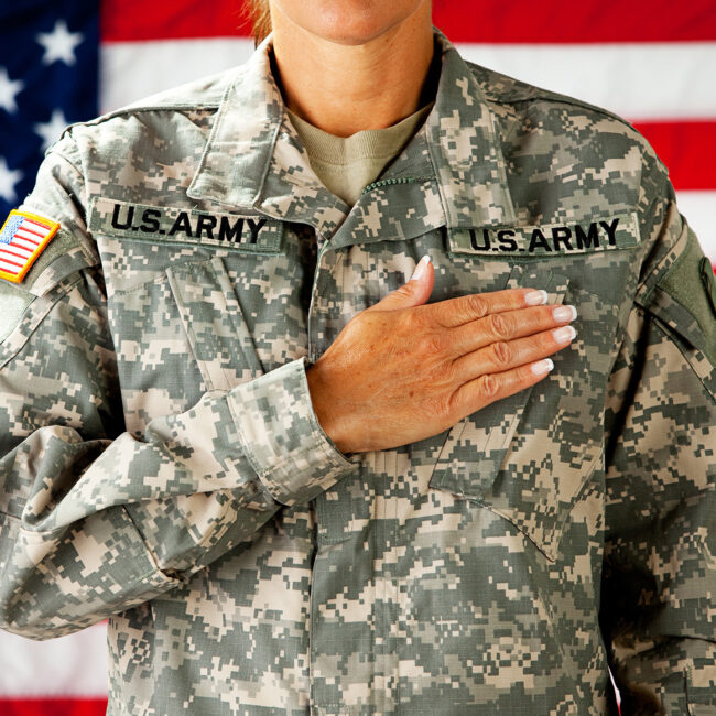 Woman soldier in the army pledging allegiance with US flag behind her; image by By Sean Locke Photography and Shutterstock