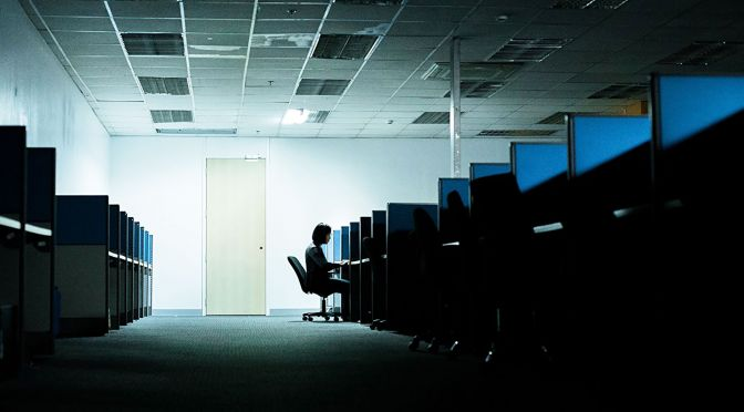 """Dark room full of cubicles with one """"cleaner"""" working late"""