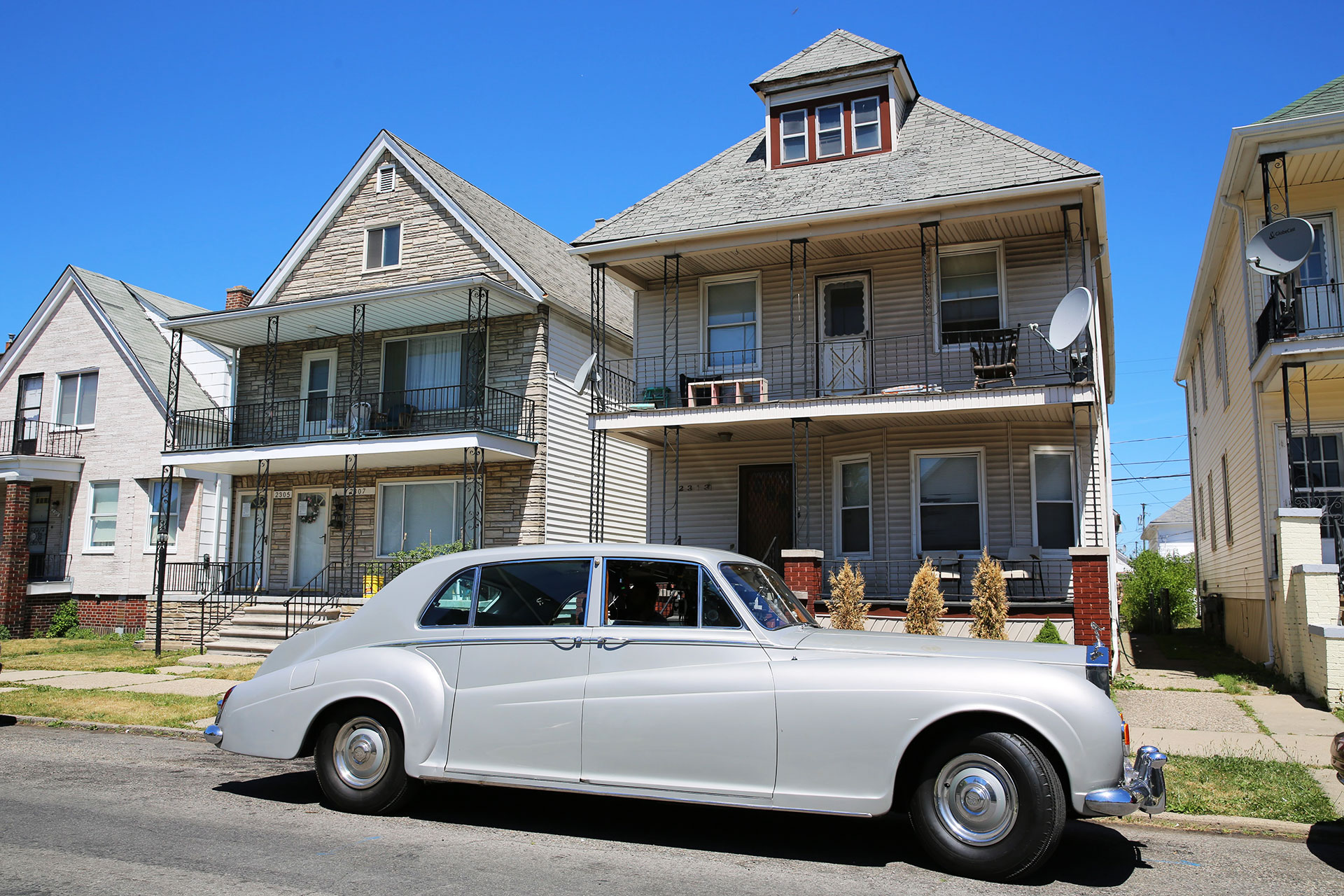 Elvis Presley's Rolls-Royce parks in front of a row house, in The King
