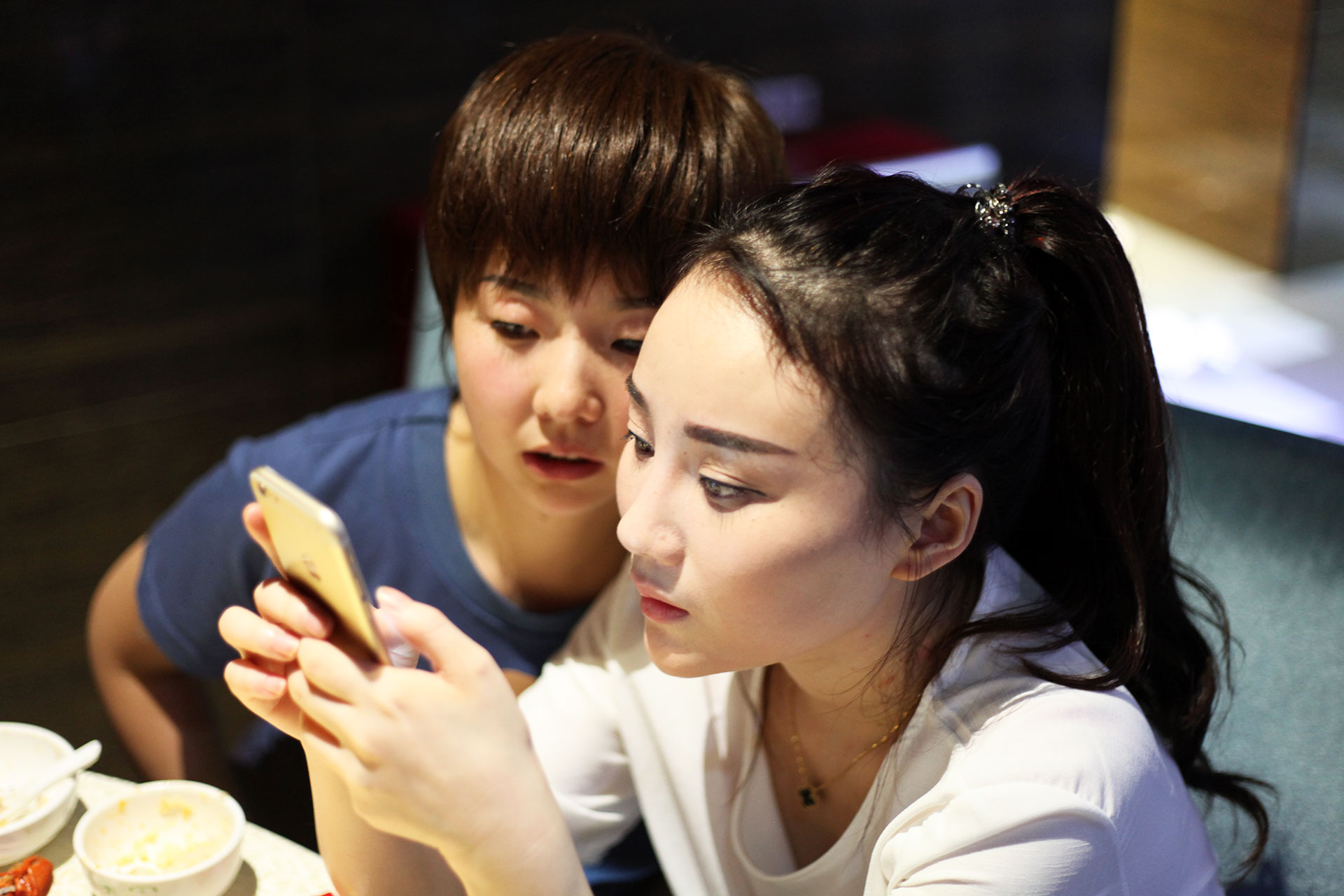 Shen Man and Dabao looking at live streaming on a phone, in People's Republic of Desire