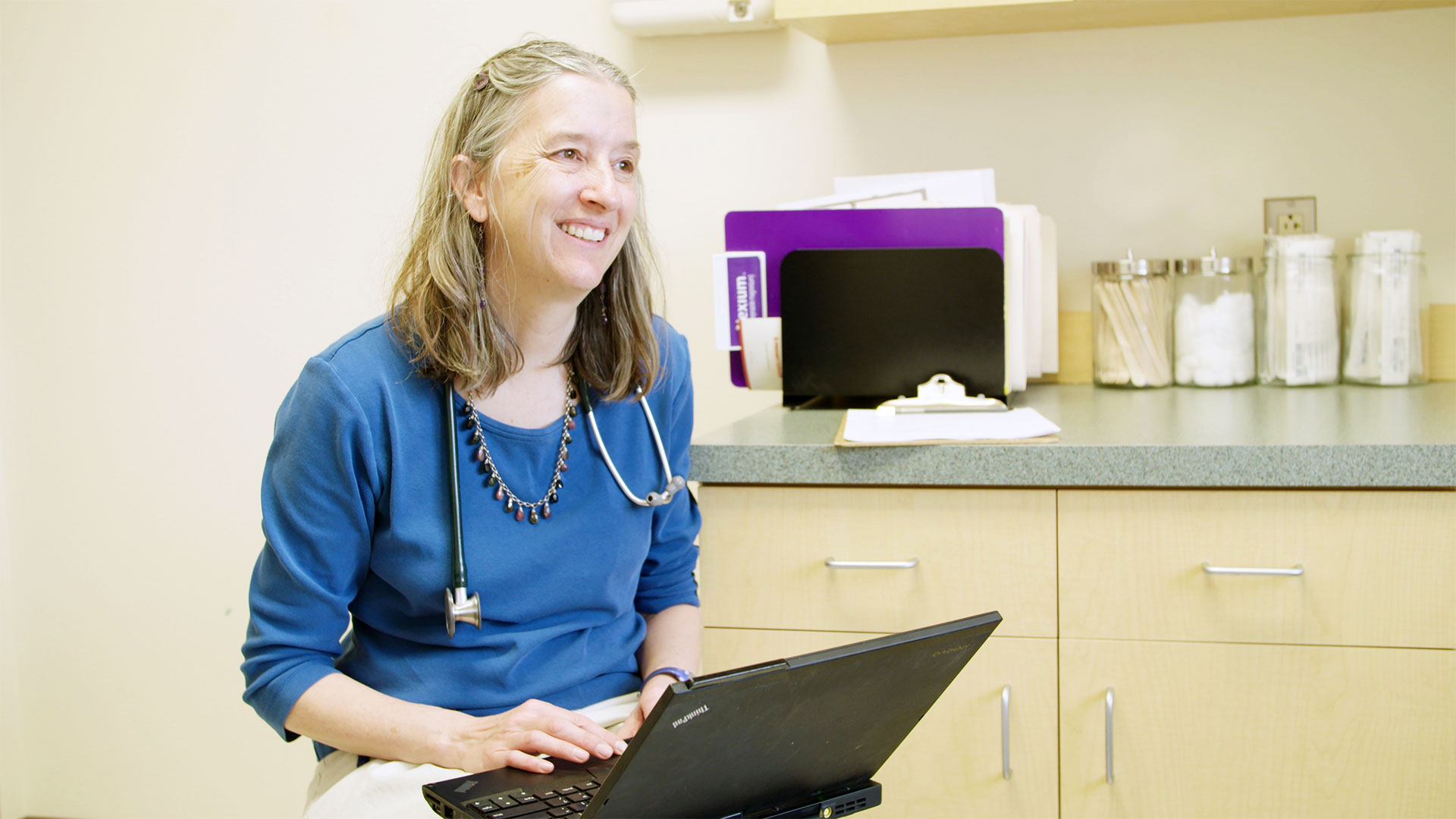 Dr Leslie Hayes, smiling at work in her office, in The Providers