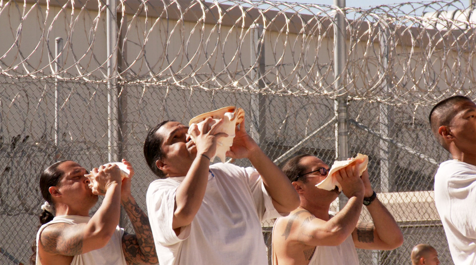Native Hawaiian prisoners perform a ritual ceremony using conch shells as instruments