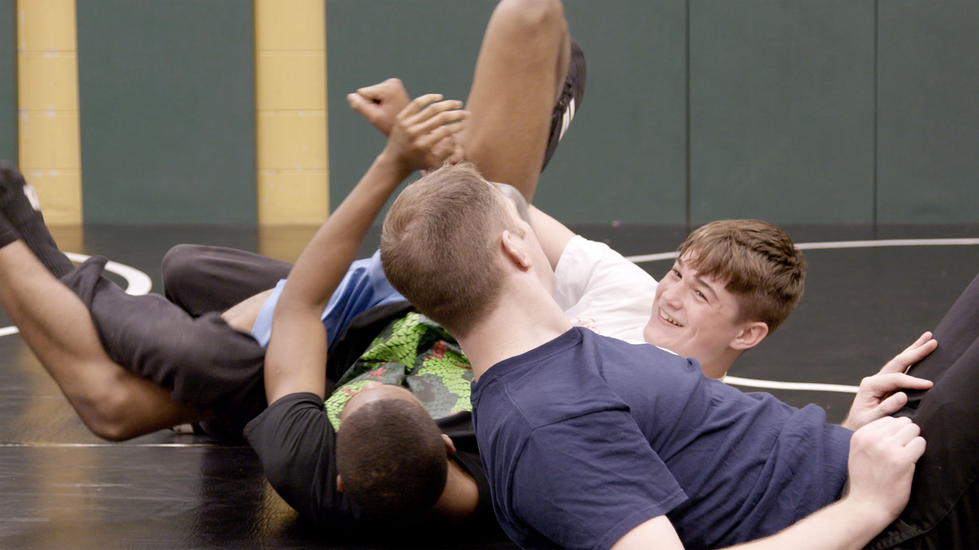 J.O. Johnson High wrestling coach Chris Scribner works on the mat with two wrestling students