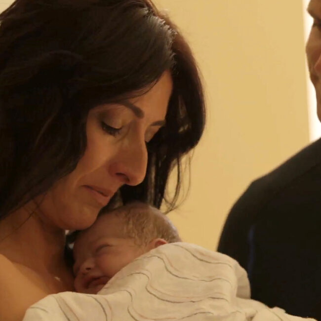 Surrogate mother Shannon holds a baby, in Made in Boise (her husband Tom looks on)