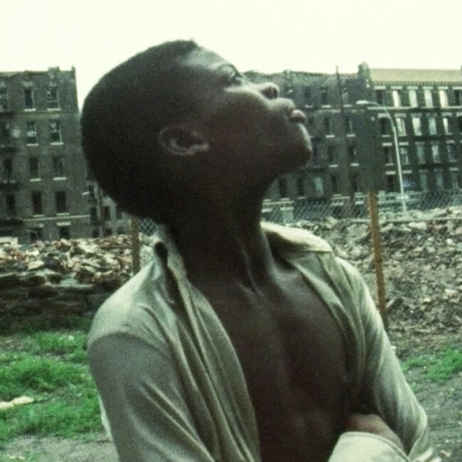 An African American boy looks up at burned out buildings in the Bronx, circa late 70s