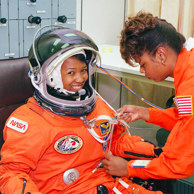 NASA astronaut Mae Jemison waits as her suit technician, Sharon McDougle, performs a unpressurized and pressurized leak check on her spacesuit, 1992.