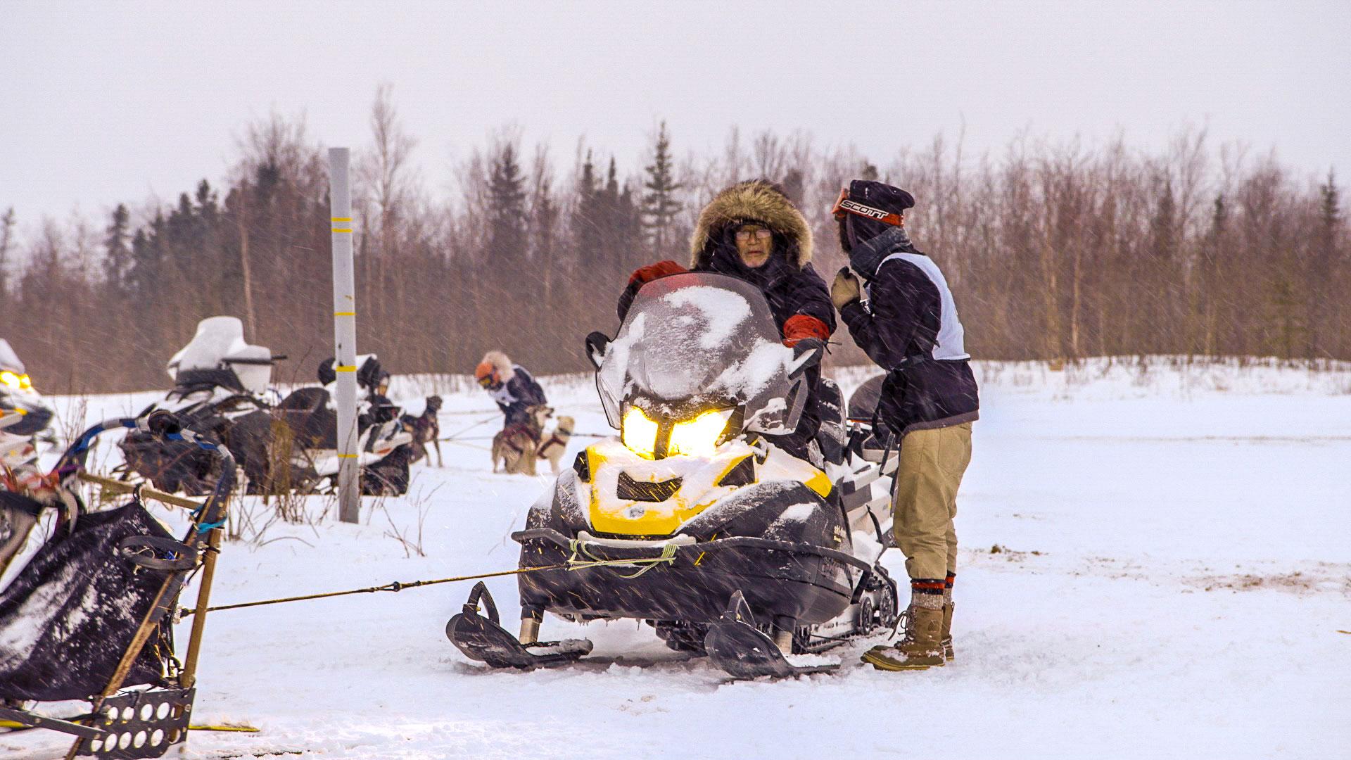 An elderly George Attla rides a snowmobile