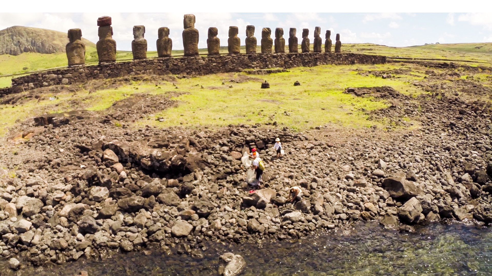 Beach cleanup under way on Rapa Nui while the famous statues loom in background